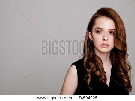 Young beautiful fashion model wearing black dress with no sleeves on grey background using hard light