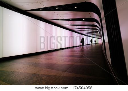 LONDON, UK - MAY 17, 2016: People walking through futuristic looking pedestrian tunnel featuring an LED integrated light wall in Granary Square exit from Kings Cross Underground station.