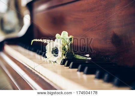 Wedding day concept. Boutonniere flower for groom on the vintage piano keys.