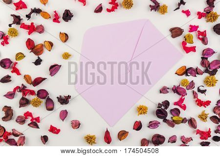 Opened envelop surrounded by colorful dried flowers petals and leaves. Top view, flat lay. Copy space for text