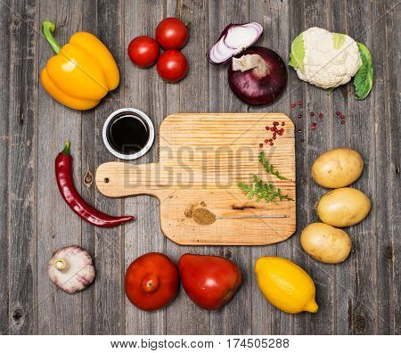 Vegetables and spices and empty old cutting board. Colorful ingredients for cooking on rustic wooden table around empty cutting board with copyspace. Top view. Retro styled.
