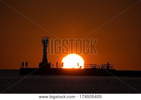 The silhouette of fishermen on Manitowoc Wisconsin's south pier as the sun peaks over the horizon.