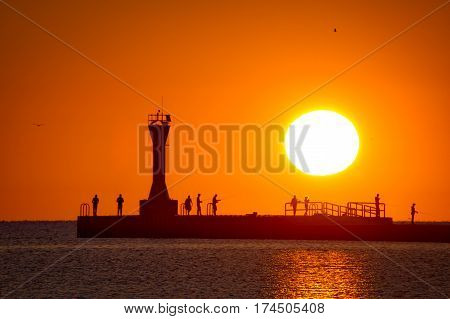 The sun rising on fishermen on Manitowoc Wisconsin's south pier reminds me of an old Nat King Cole song called Orange Colored Sky.