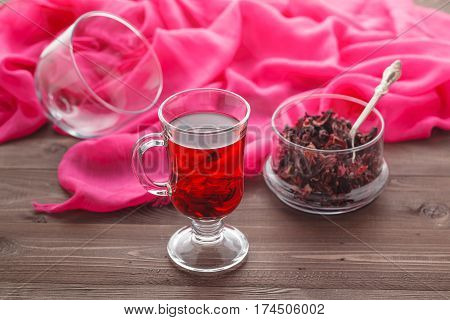 Transparent Cup Of Hibiscus Tea On A Background Of Dry Tea
