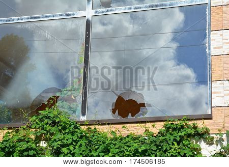 Broken glass window reflecting cloudy sky. A house window with a broken window pane outdoor.