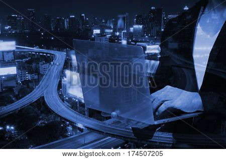 double exposure of smart businessman using laptop with blurred city night background.