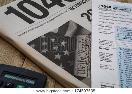 Tax preparation form US 1040 and instructional booklet with calculator on wooden board