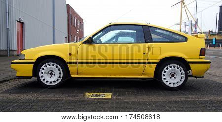Den Helder, The Netherlands - February 19, 2017: Yellow HONDA Civic Coupe CRX 1.6I 16V parked in a public parking lot. Nobody in de vehicle.