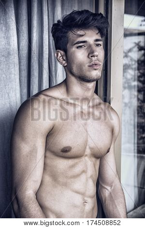Sexy handsome young man standing shirtless outside next to window curtains