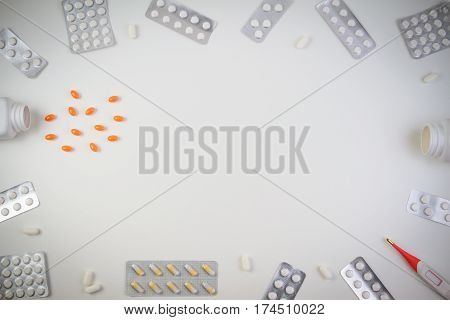 Pills border background. Vitamins, tablets, pills in blister pack, drug bottles and capsules spilling out of a bottle, thermometers on white background. Top view. Copy space for text