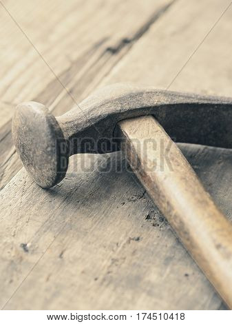 Old used vintage hammer on a wooden workbench