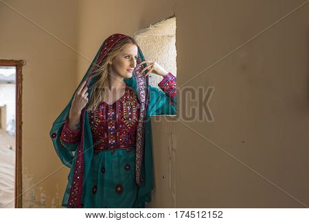 A woman in traditional omani dress in an abondoned village in a desert