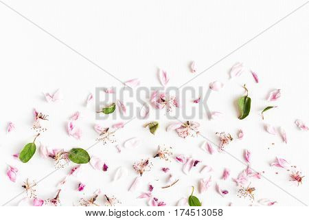white background filled with wilted sacura flowers and leaves. Concept of love and spring. Dof on sacura flowers. top viev.