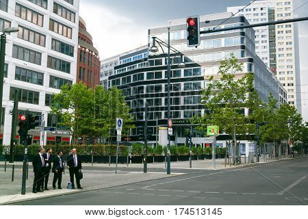 Berlin, Germany - September 7, 2014. Mens businessmen in the same business suits with cases in the business quarter are crossing the street.
