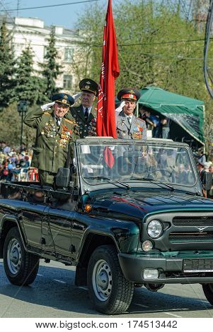 Tyumen Russia - May 9. 2009: Parade of Victory Day in Tyumen. Banner group of World War 2 veterans on SUV salute on parade