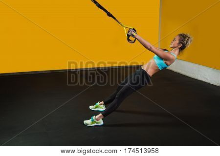 Sporty woman doing exercises with suspension straps at contemporary gym, copy space for text. Suspension training for strong body