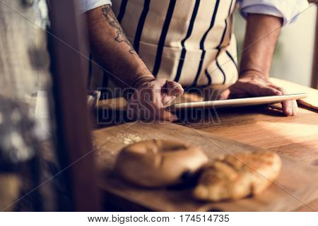 Chef baking pastry homemade and using tablet