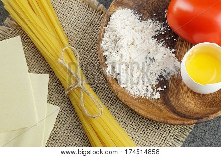 Basic ingredients for cooking Italian pasta: fresh red tomatoes bavette eggs flour and sheets of lasagne on sackcloth and dark background.