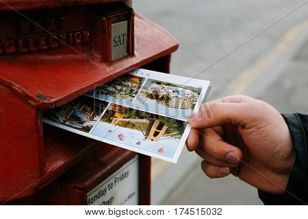 LONDON, UK - DECEMBER 27, 2016: Male hand is putting a postcard in an iconic red postbox belonging to Royal Mail.
