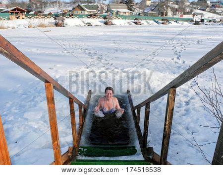 Women plunge into the winter ice-hole in lake after a sauna.