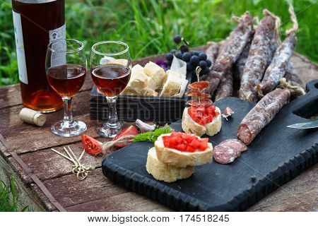 Bruschetta, Slices Of Baguette Garnished With Garlic, Tomato And Sausage, Close Up On A Wooden Board