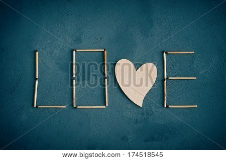 Texture of concrete and blue or green paint plaster. On the texture matches arranged in the form of the word Love. In the middle of the letters have a wooden natural heart. Horizontal backgraund. Valentine's Day. World day of the match.