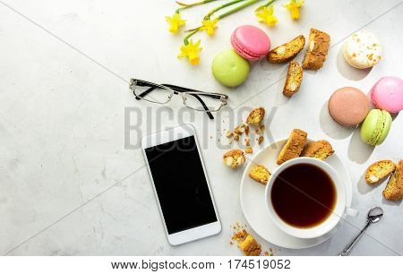 Cup of black tea with tasty almond cookies rich in vitamins minerals varicolored macaroons smartphone glasses and flowers on a white background in light key. Top view copy space.