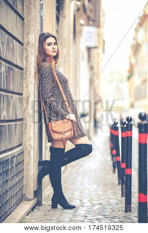 Beautiful woman outdoors in the city. Fashion and youthful charm. Woman with her purse, dress and boots in the historic center of Rome, Italy.