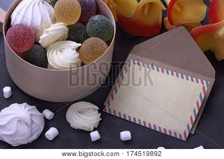 Bouquet Of Red Yellow Callas With Marshmallows Marmalade In A Wooden Round Box And Envelope On Gray