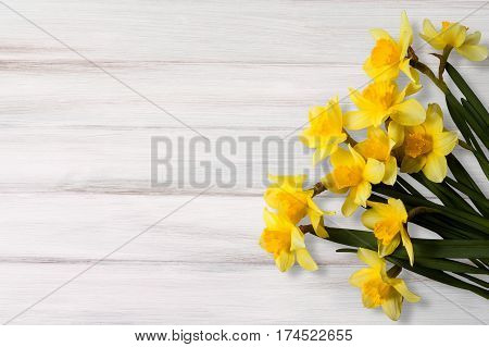 Greeting Card for Easter Mother's Day Birthday March 8. Beautiful background with yellow jonquil flowers on wooden texture.Top view Flat lay. Horizontal Image With Copy Space