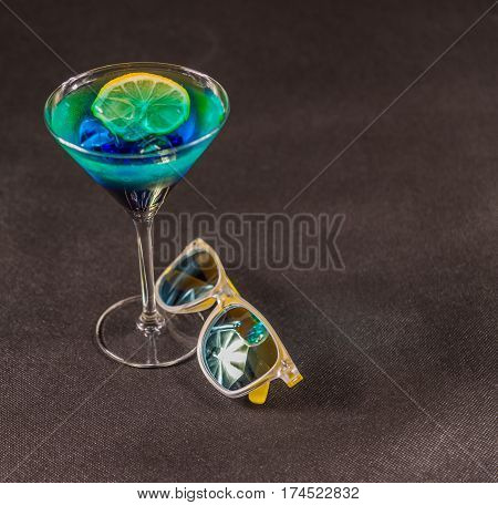 right side view on a colored drink a combination of blue and green lemon martini glass yellow sunglasses party set