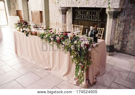 Wedding table decoration with the pink flowers, pomegranate and greenery for the fiance and fiancee