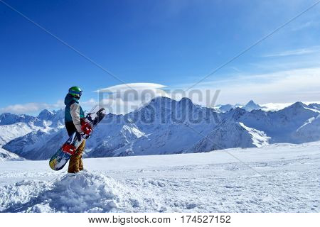 snowboarder standing with snowboard in the mountains. Beautiful winter landscape with ridge, blue sky in the background. Photo on a theme of extreme sports, winter sports, snowboarding.