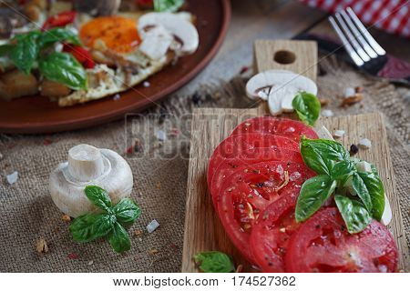 Fried eggs with mushrooms tomatoes and basil