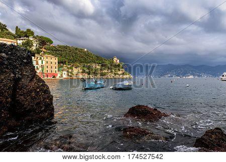 Stormy sky and small boats in sea bay of Portofino town. Portofino is small fishing town in Liguria district, Italy.