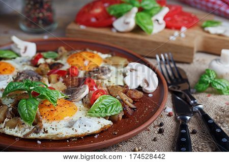 Fried eggs with mushrooms tomatoes and basil on rustic wooden table. Natural food concept