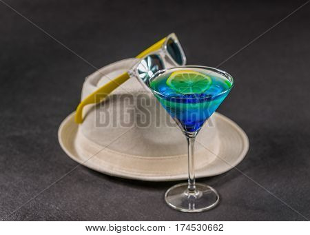 colored drink a combination of blue and green lemon martini glass yellow sunglasses on white hat party set