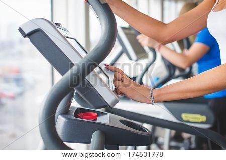 The girl chooses exercise regime on the elliptical trainer