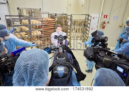 MOSCOW, RUSSIA - MAY 18, 2016: Reporters interview head of department of trade and services of Moscow Alexey Nemeryuk at plant Russian Fish Factory during Fish Week. Inscription Russia at microphones.