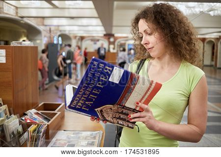 MOSCOW, RUSSIA - JUN 14, 2016: Woman looks through album State Tretyakov Gallery (inscription on book) at Tretyakov Gallery - Museum of Art founded by merchant P. Tretyakov.