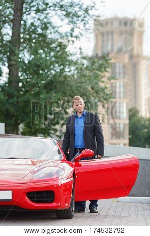 MOSCOW, RUSSIA - JUN 22, 2016: successful businessman (with model releases) sits behind wheel of luxury red roadster Ferrari