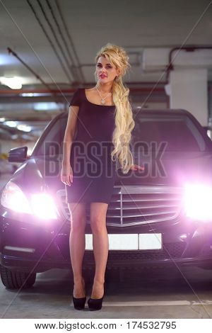 MOSCOW - JUN 01, 2015: Beautiful girl  with long blond hair in a black dress standing near black car with lights on