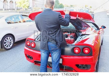 MOSCOW, RUSSIA - JUN 22, 2016: Successful businessman  raises hood on luxury roadster Ferrari, seen from behind