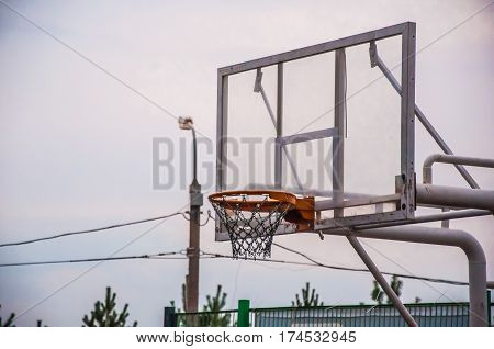 A basketball hoop without a ball inside on the background of the city