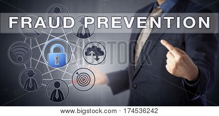 Business man in blue suit is pointing at FRAUD PREVENTION caption. A virtual padlock icon is lighting up amidst a computer network diagram. Information technology metaphor and data security concept.
