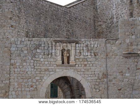 A statue of St Blaise holding a model of Dubrovnik on the wall of fortress in the old town Dubrovnik in gloomy evening