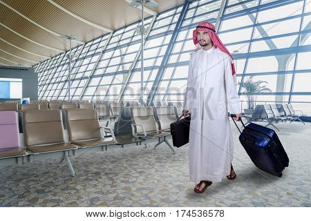 Portrait of Arabian businessman carrying a briefcase and luggage while walking in the airport terminal