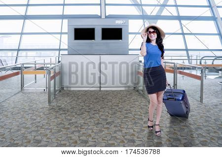 Full length of attractive young woman standing in the airport terminal while carrying a luggage