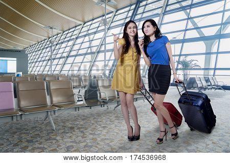 Two beautiful young women standing in the airport terminal while carrying their luggage and looking at something