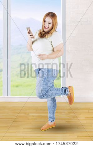 Full length of a happy blonde girl reading a sms message on her mobile phone near the window at home
